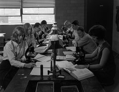 Students seated in biology laboratory with microscopes