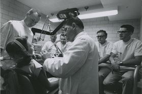 Dental faculty works on patient as students look on
