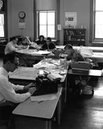 Students working at tables and typewriters