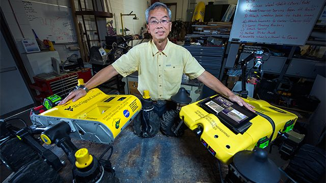 A WVU professor posing with two WVU-branded robots