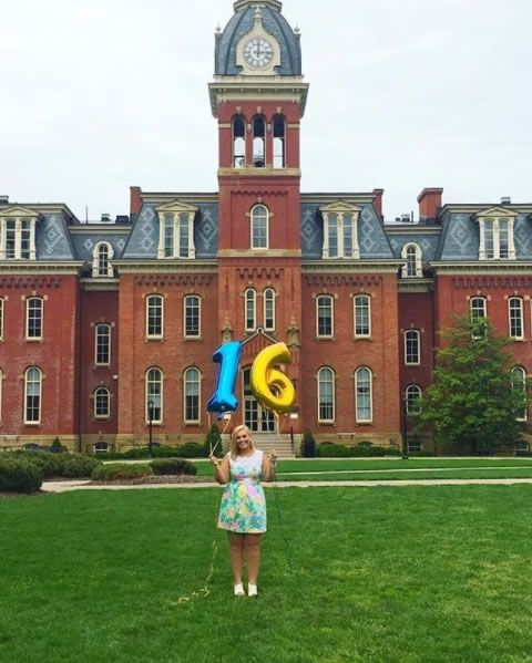 "Holding ""one"" and ""six"" balloons in front of Woodburn Hall"