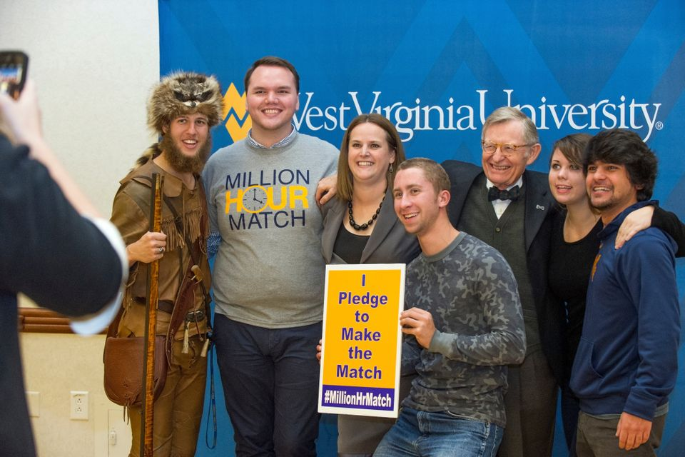 "President Gordon Gee posing for a photo with students who are holding a sign that says ""I pledge to make the match"""