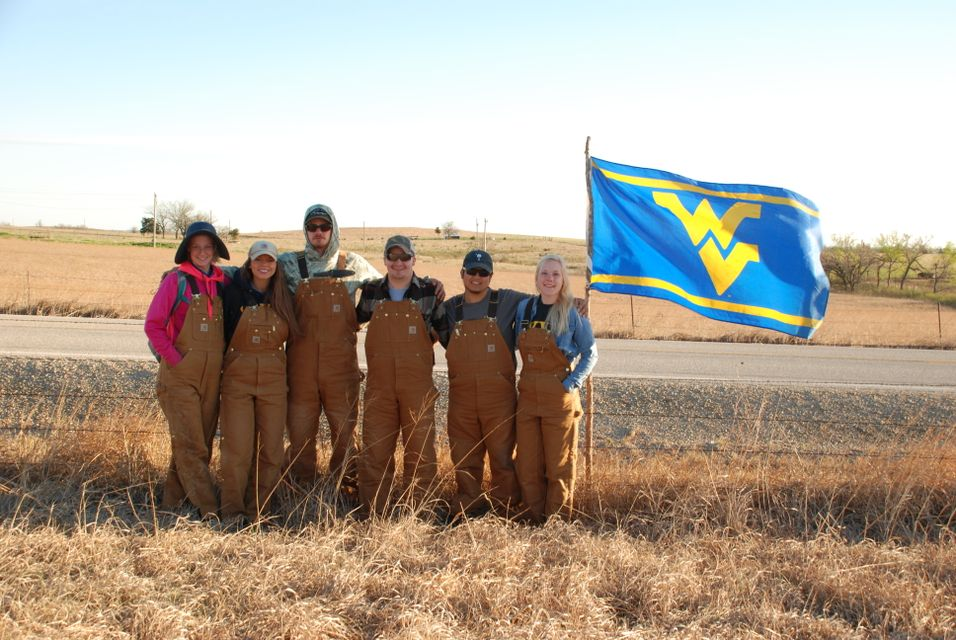 "WVU's Soil Judging Team in a field with a ""Flying WV"" flag"
