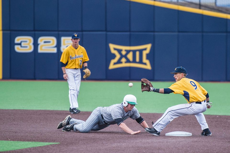 A WVU baseball second baseman attempts to catch a base runner from stealing