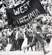 Mountaineer mascot carries West Virginia flag