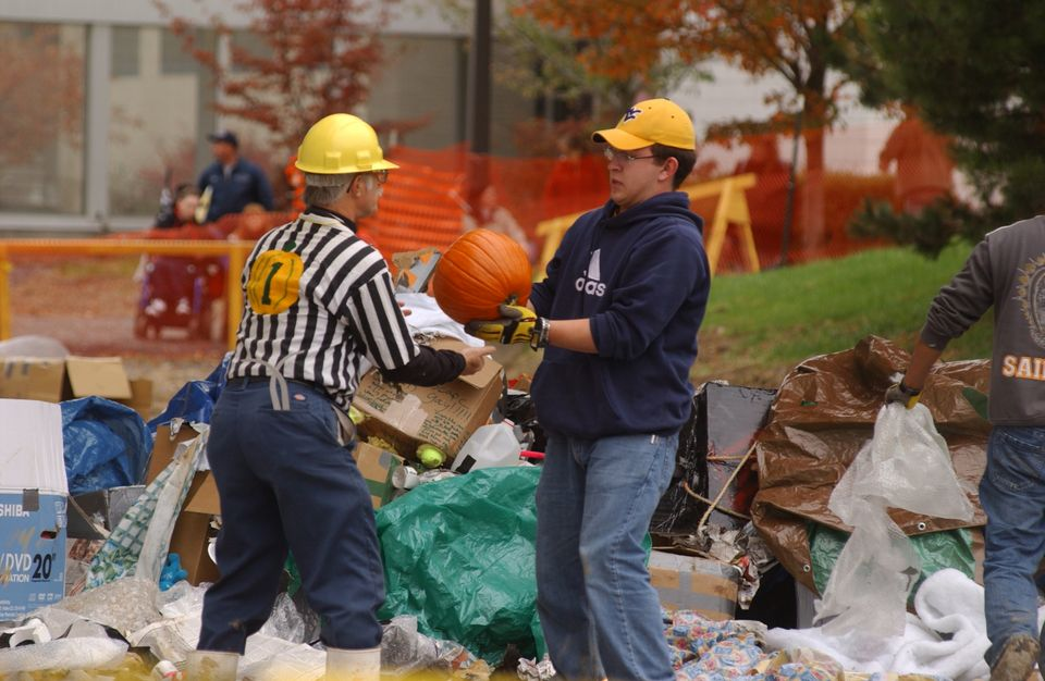 Workers survey a pumpkin for breaks after it was dropped from the top of the Engineering Sciences Building