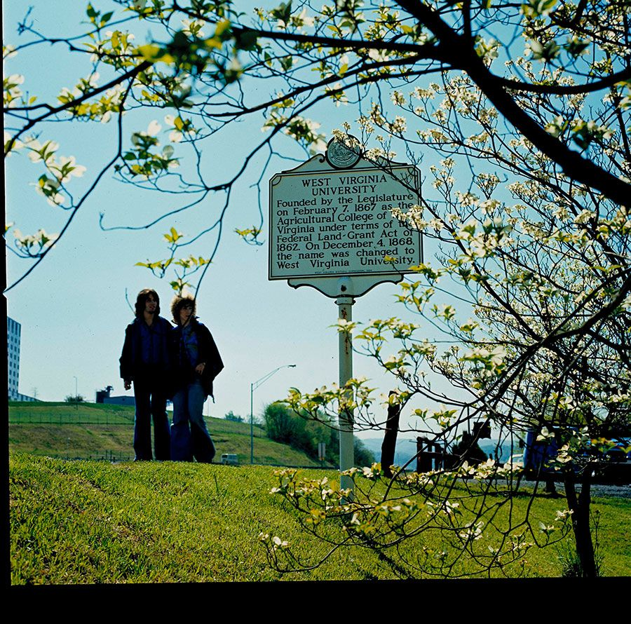 Students walking by WVU sign