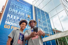 Father and son take a selfie in front of the Mountainlair banner