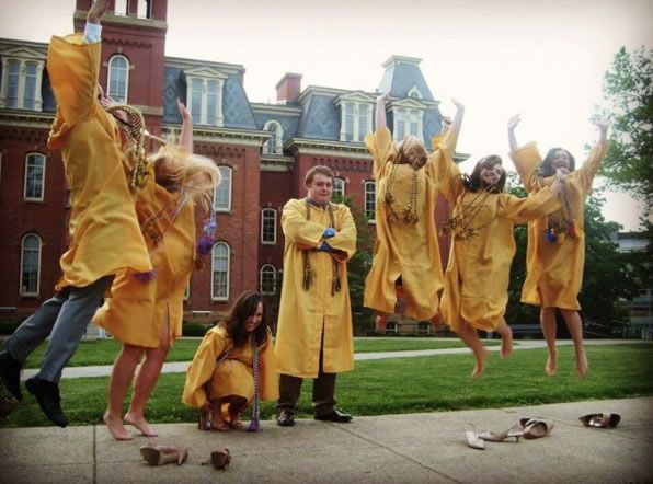 Graduates jumping in front of Woodburn Hall