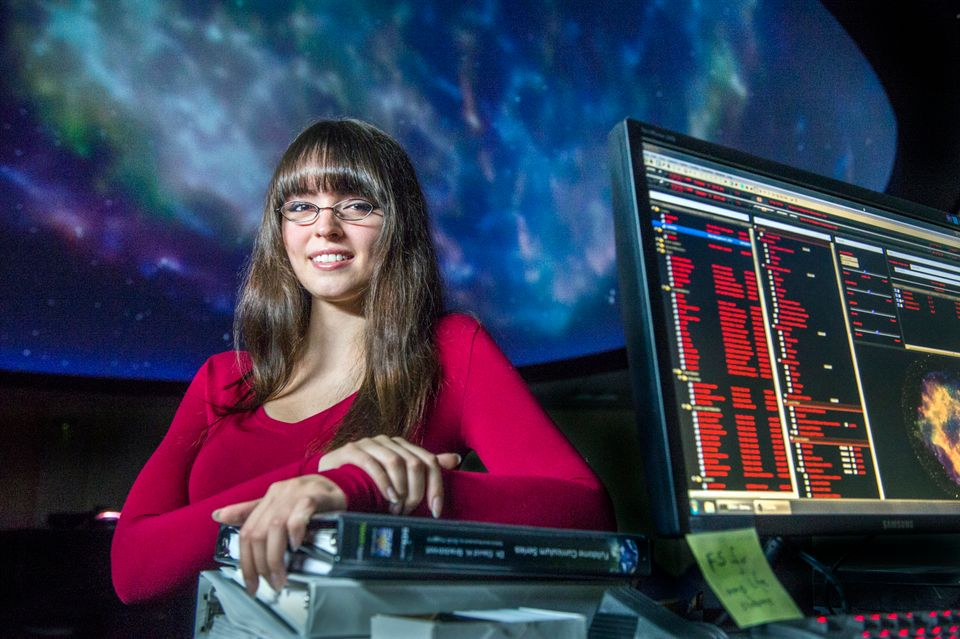 A student smiles in front of a projection of stars in the planetarium