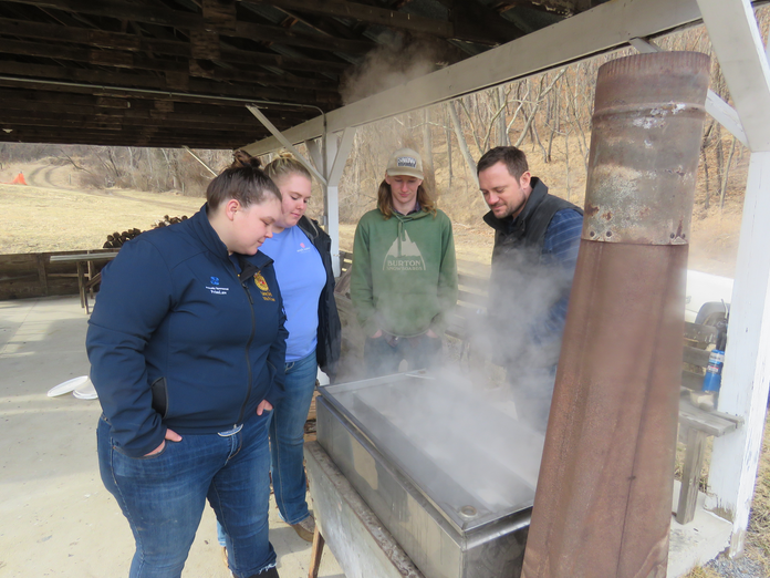 WVU Potomac State College Students (l-r) Lainey Smith, an agriculture education major from Red House, W.Va.; Madison Jackson, a SAGE major from Greenbrier County, W.Va.; and Kyle Cessna, a SAGE major from Cumberland, Md., along with SAGE Program Director Corey Armstrong, check out the sugar maple sap as it cooks to see if it's turning to syrup.
