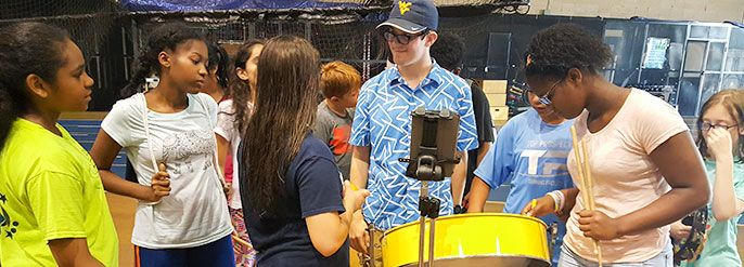 Students learning to play a steel drum