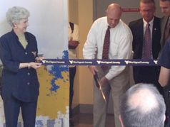 Lois Morris holds the ceremonial ribbon as WVU former President James Clements cuts the ribbon