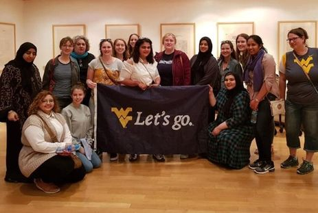WVU students, joined with RUW students, hold a 'Let's Go' WVU Flag in Bahrain.