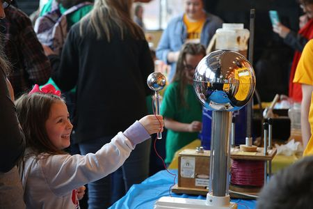 A young girl, smiling, interacts with a static ball during a STEM exploration activity.