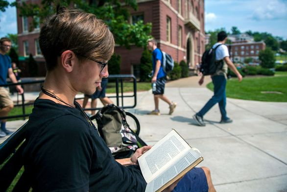 Student reading book on campus