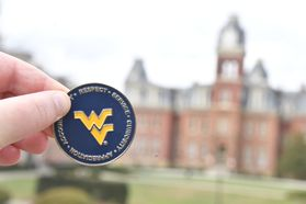 Blue and gold front of WVU Values coin, flying WV in the middle with the values of service curiosity respect accountability and appreciation surrounding.