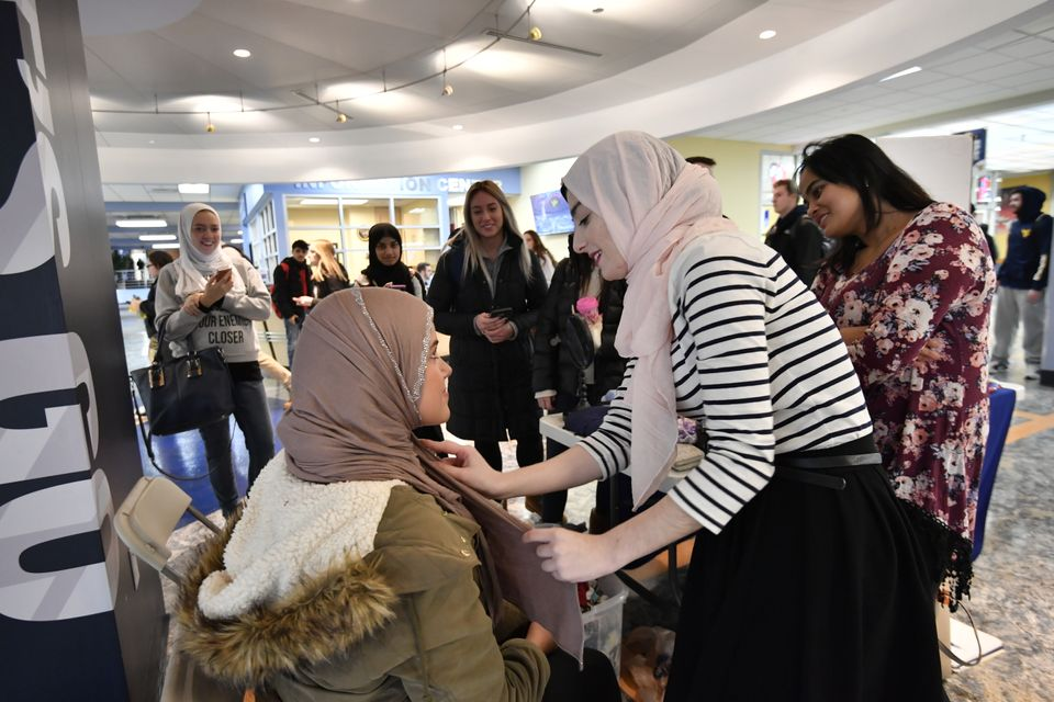 WVU Muslim Students Association member helps a student put on a hijab