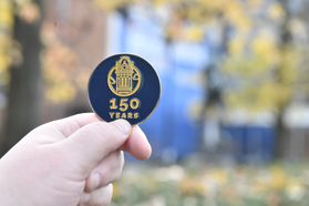WVU's 150 seal printed in gold on navy background. Seal is the tower of Woodburn with the words 150 years