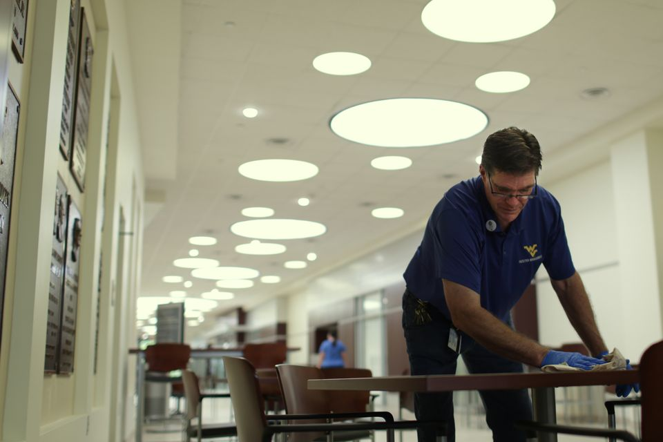 WVU facilities worker cleans tables