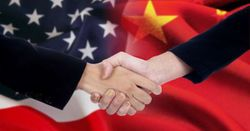handshake in front of a US flag and a China flag
