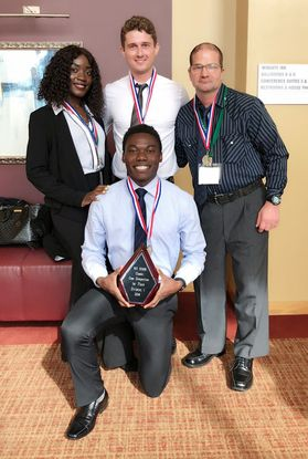 Four member of the SHRM case team stand with their award plaque commemorating their win.