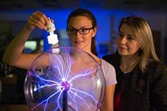 A female student holds a light bulb up to a plasma ball as a female professor looks on. The plasma ball's purple tendrils rise up to the bulb, causing it to illuminate.