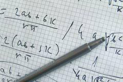 An ink pen lies on top of a piece of graph paper, upon which multiple mathematical equations are scribbled.