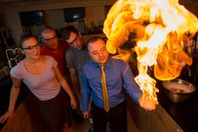 At right, a professor stands in a lab with a massive ball of flame rising from his hand while three students look on in astonishment.