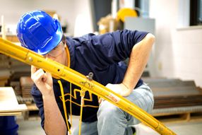 A male student in a blue hard hat inspects a piece of yellow steel.