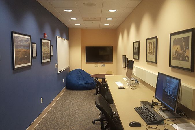 student veterans's room with tables, chairs, computers, and large screen.