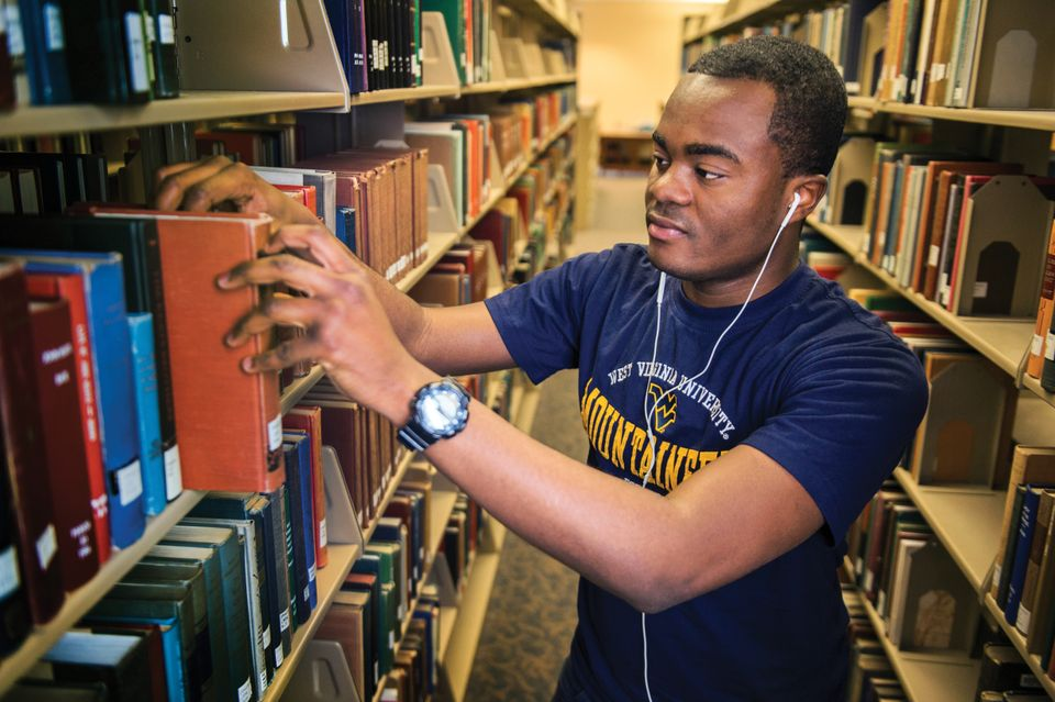 Student reaching for book off library shelf