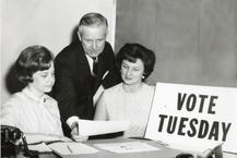 Arch Moore with two women with sign reading Vote Tuesday