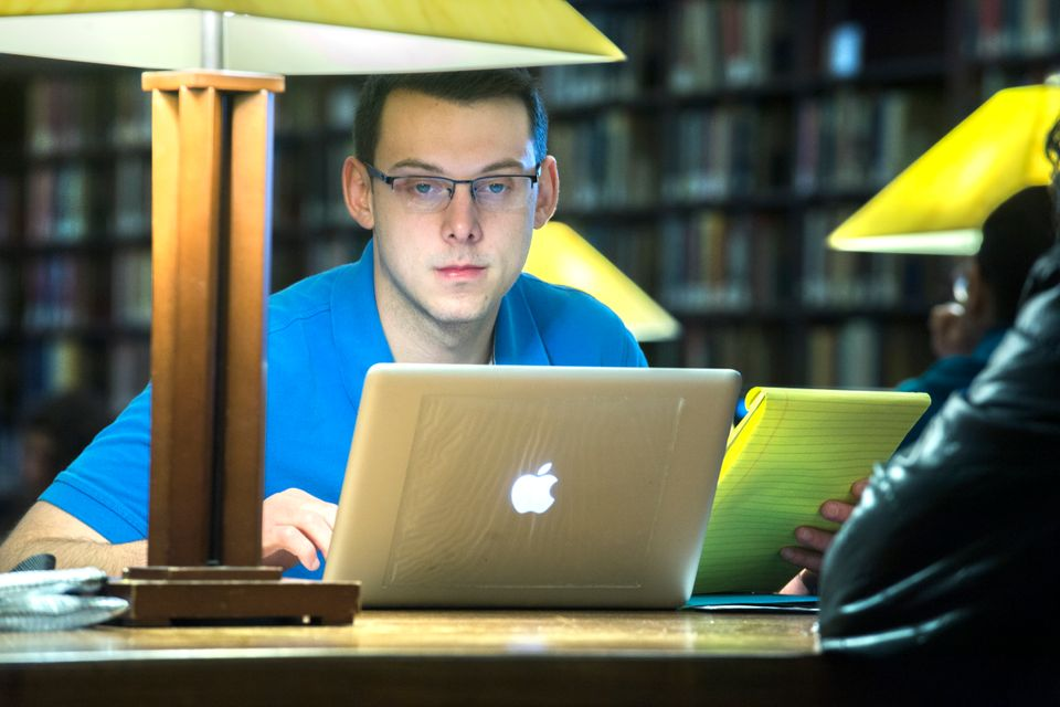 student studying in quiet reading room with computer