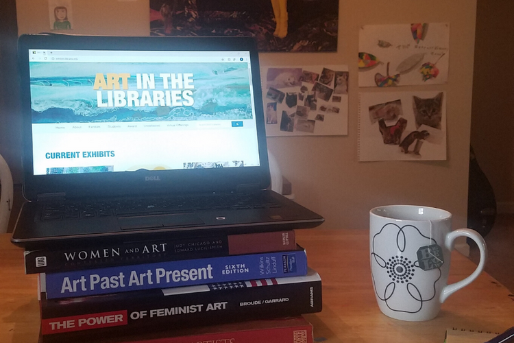 laptop sitting on art books showing art in libraries website next to cup of tea and paper and pen