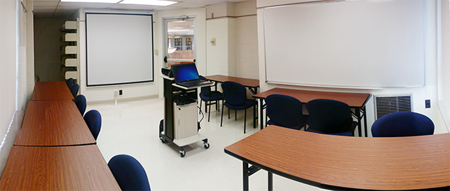 Room with 6 tables, 12 chairs, white board, and projector screen.
