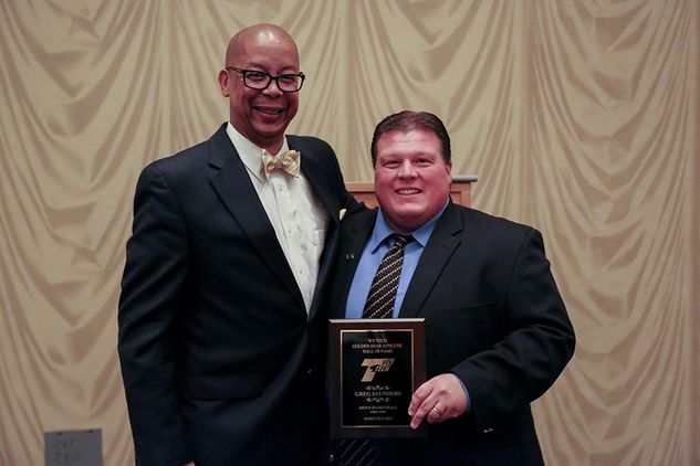 Hall of Fame recipient poses with athletic director holding Hall of Fame plaque