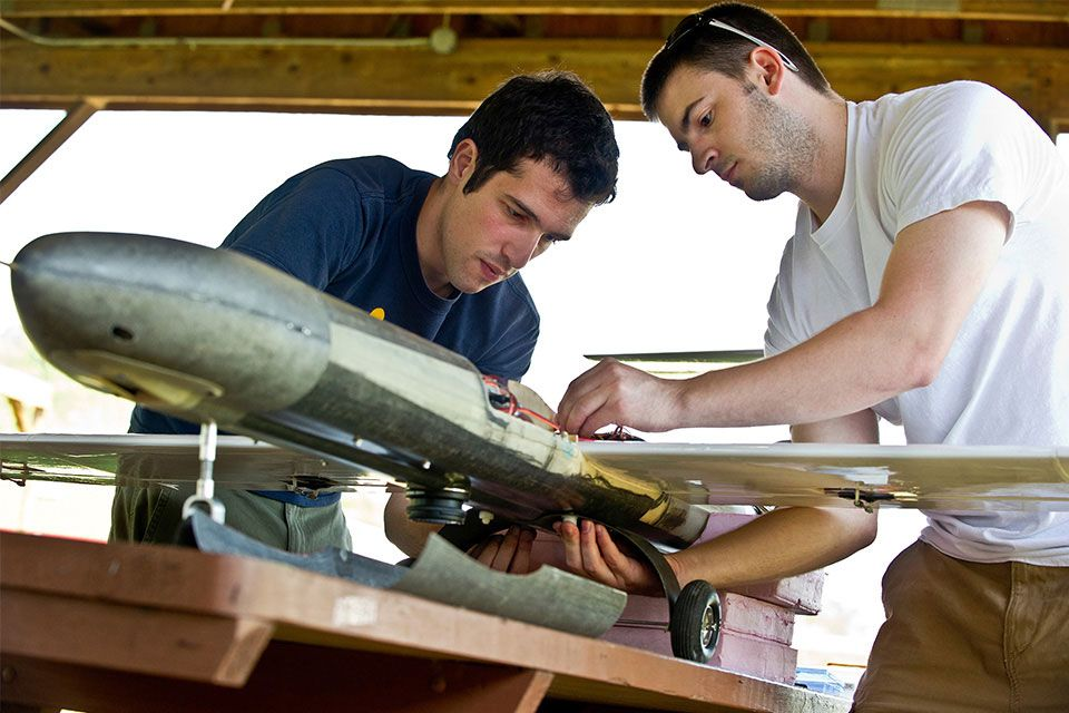 Two students working on a drone plane