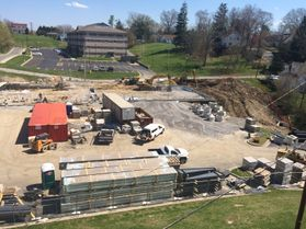 A scene of the construction of WVU Tech's Elab building, where trucks and materials are scattered over the packed dirt of the construction site.