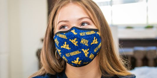 A student wearing a WVU branded mask in a WVU Potomac State College dorm room