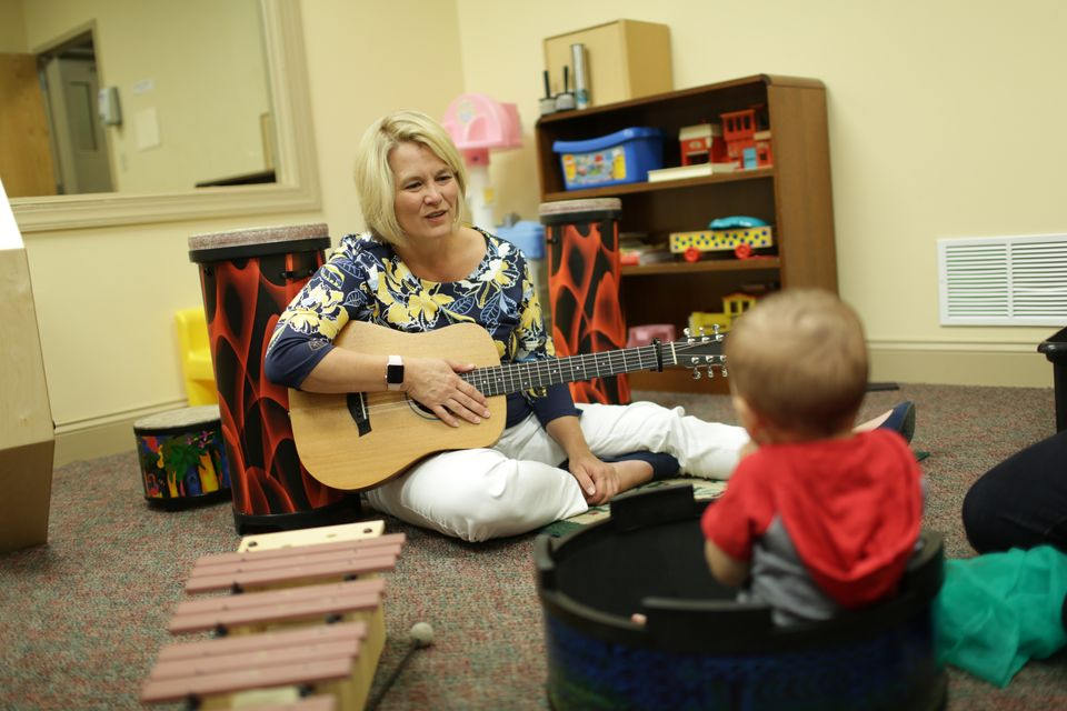 WVU Music Therapist plays guitar with client