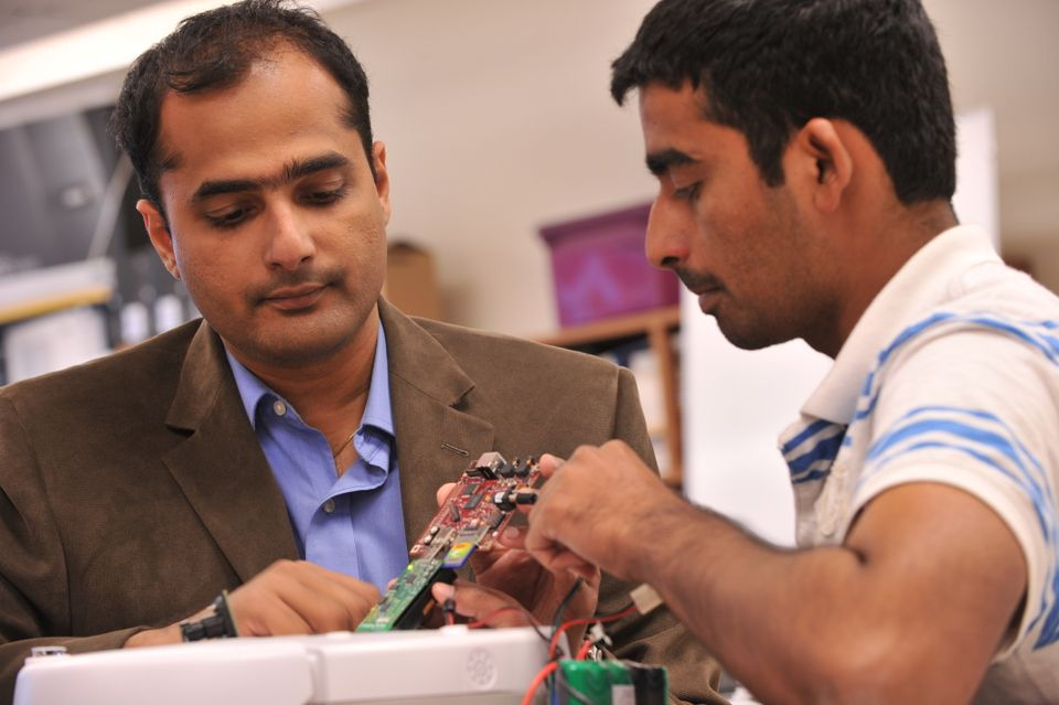 Two employees work together on engineering piece
