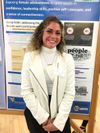 Portrait of Caitlyn Lyons in front of her poster on research day