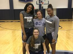 Abby Reid and three Georgetown women's basketball players take photo.