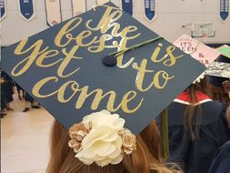 "A graduating student whose hat says ""the best is yet to come"""