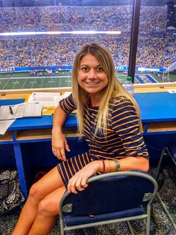 Samantha sitting in the press box at mountaineer field during a game
