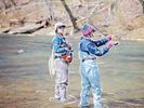Anne and Kim fly fish in a shallow stream