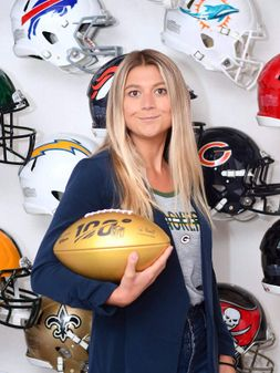 Samantha posing in front of NFL helmets holding a golden football