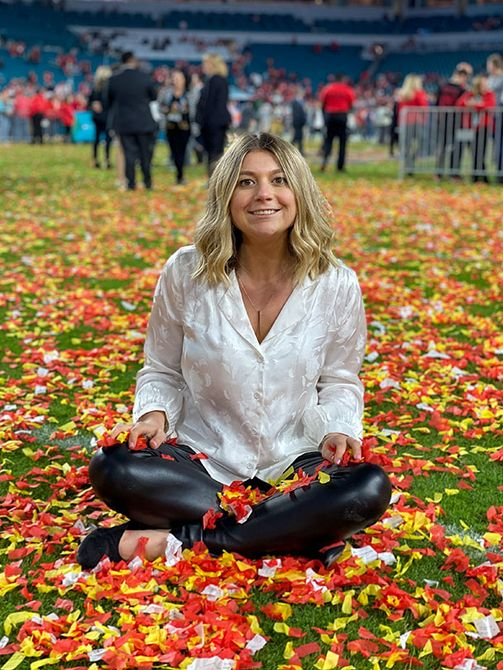Samantha sitting on the field after the chiefs won the super bowl.