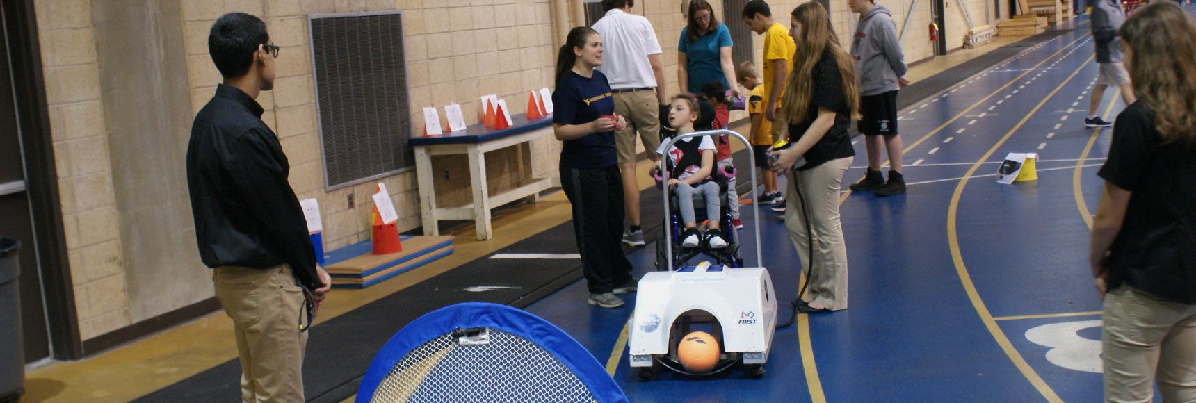 Students using a ball kicking robot